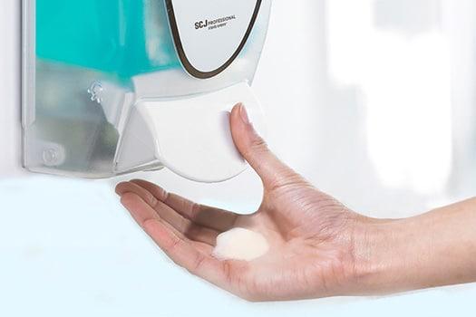 Eine Hand unter einem Seifenspender